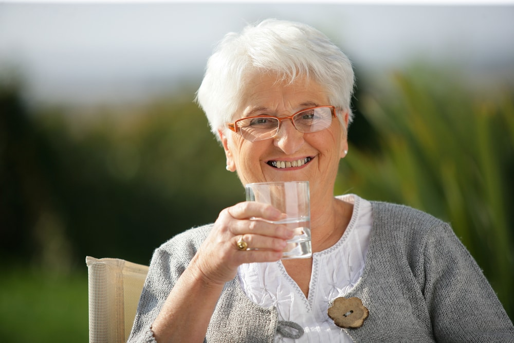 Senior woman drinking water to protect herself from heatstroke