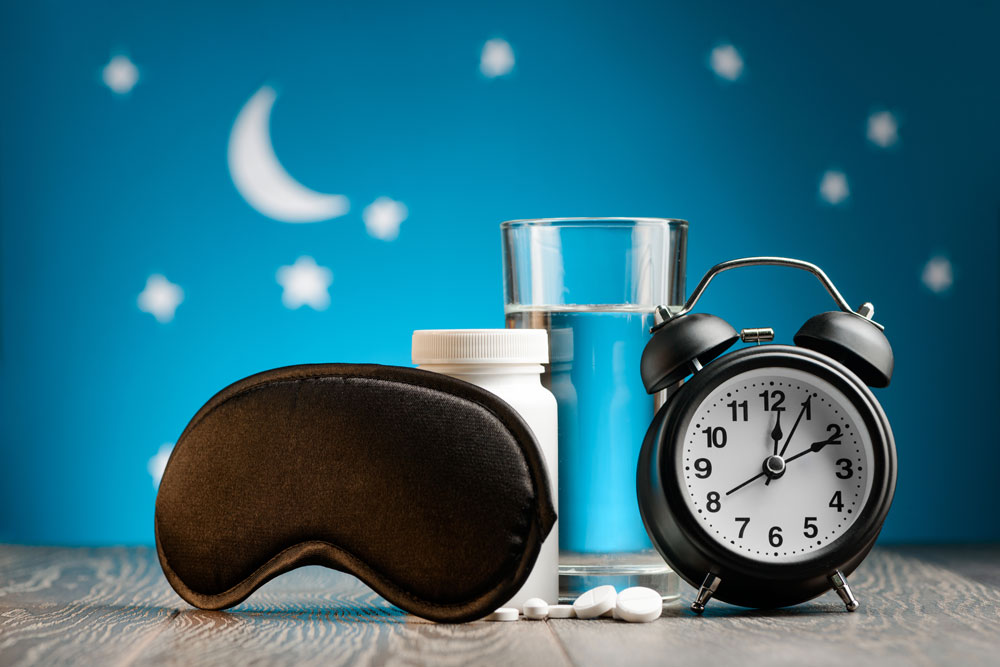 Sleeping pills, eye cover & a glass of water. Sleep remedies for older adults.