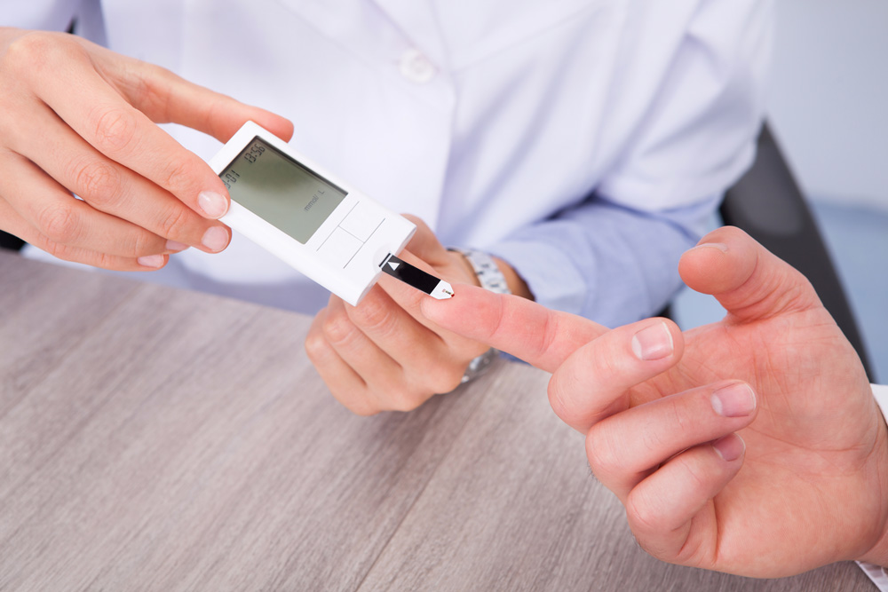 Doctor checking sugar levels of a patient suffering from diabetic foot ulcers
