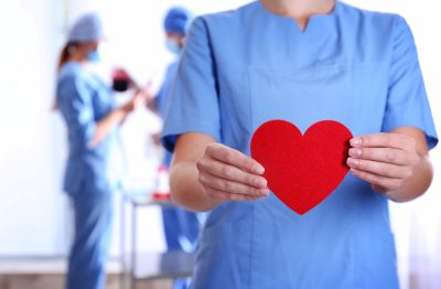 doctor holding red heart at hospital for wound care awareness