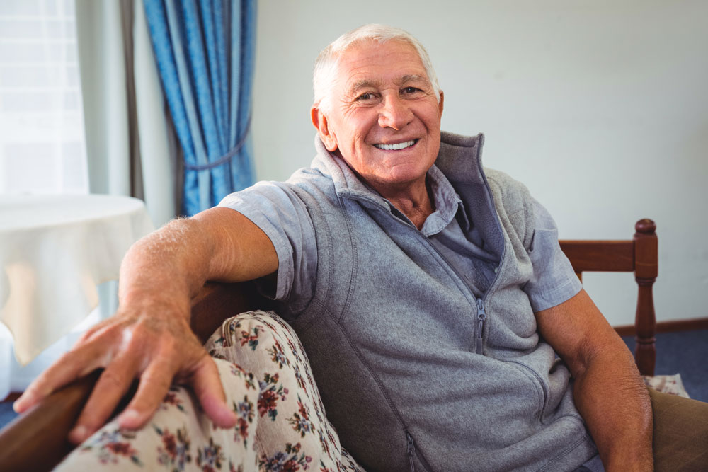 Senior man sitting on couch enjoying long-term nursing care