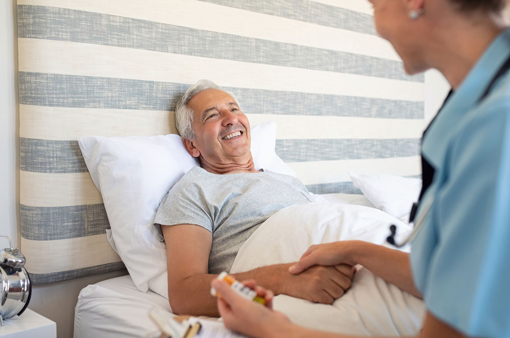Cheerful senior man receiving health care and staying at nursing home