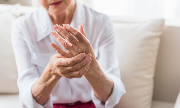 Elderly woman massaging her hand to reverse rheumatoid arthritis