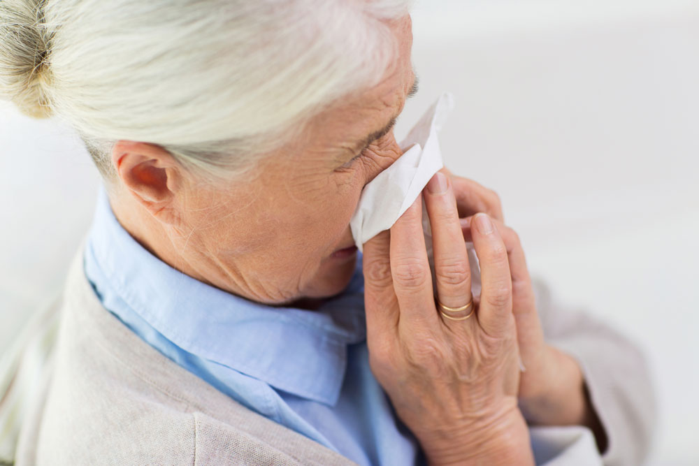 Sick senior woman blowing nose to paper napkin to protect herself and others from COVID-19