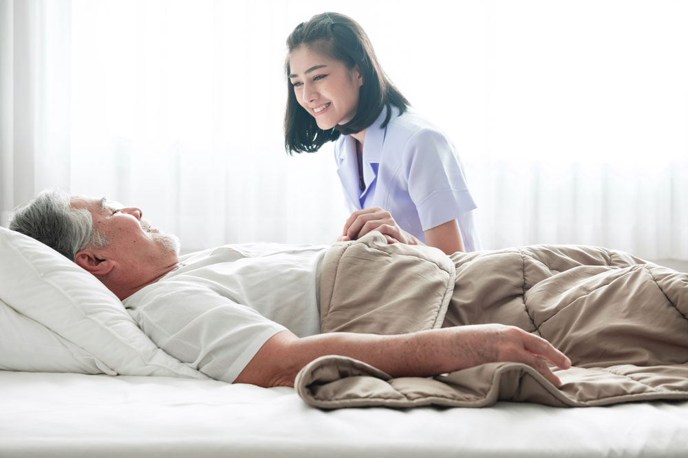 Senior man with pressure ulcers on bed and nurse waking him up
