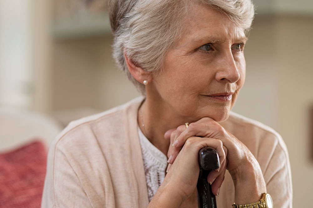 Senior woman suffering from memory loss sitting on couch holding walking stick