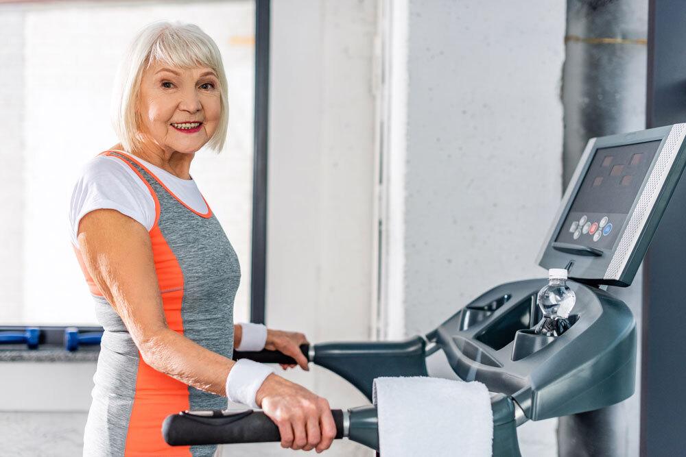 Happy elderly women doing exercise on treadmill machine to avoid bone loss