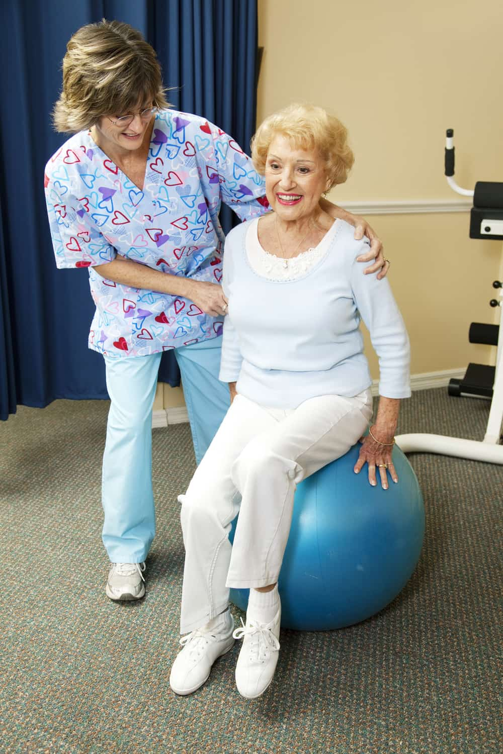 Nurse helping elderly woman doing physical therapy exercise using gym ball