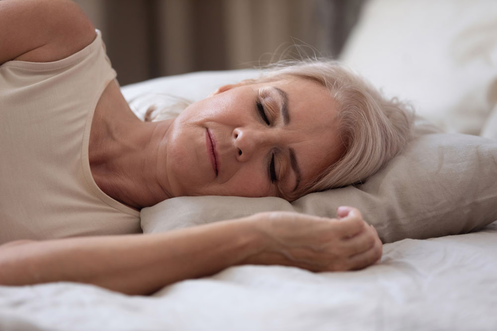 Elderly woman with diabetes sleeping on the bed alone