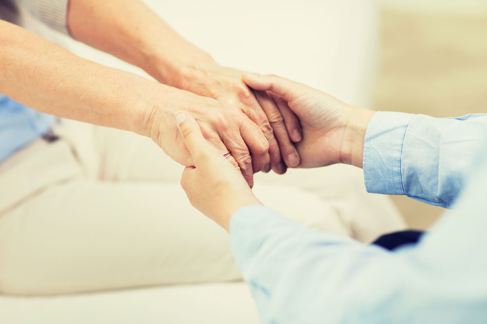 Nurse holding hands of an elderly woman and providing emotional support
