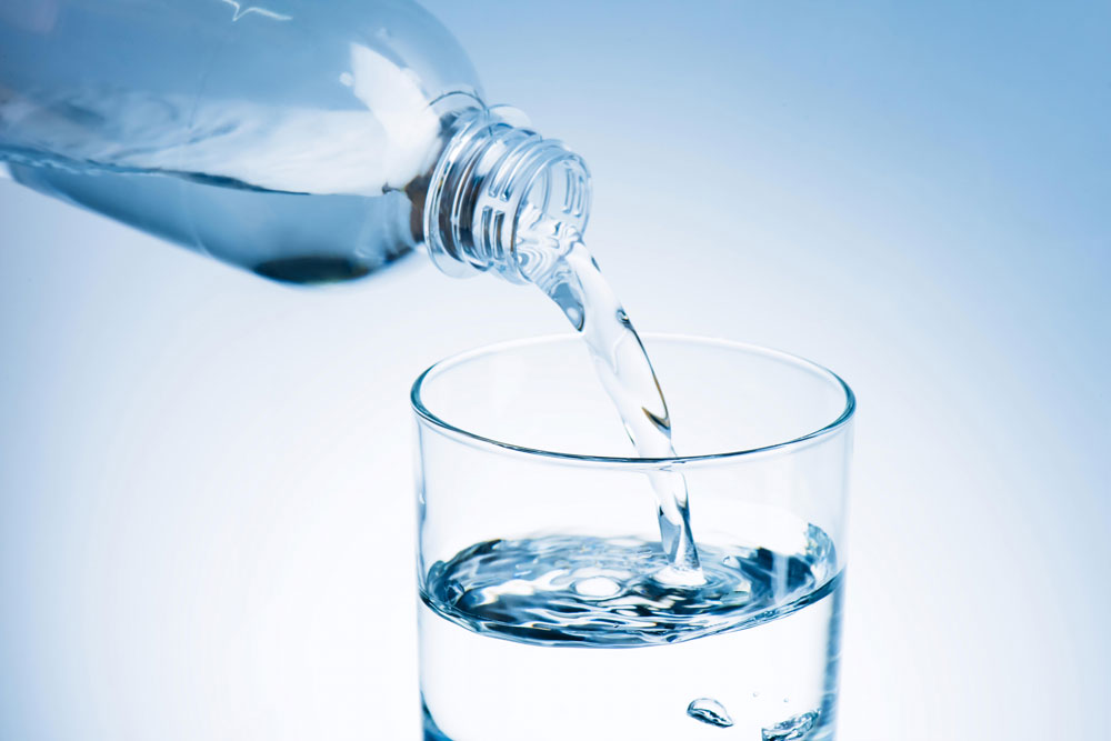 Pouring water in glass from bottle to keep hydrated and avoid allergy triggers