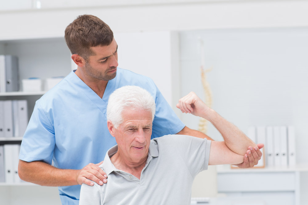 Therapist helping senior man with shoulder disorders