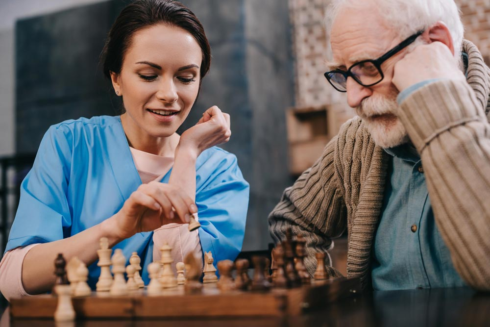 Elderly man playing chess with female nurse during brain exercises