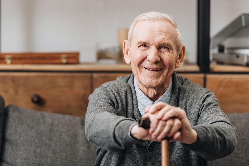 Cheerful old man living a happy life after a stroke sitting on sofa smiling and holding walking cane
