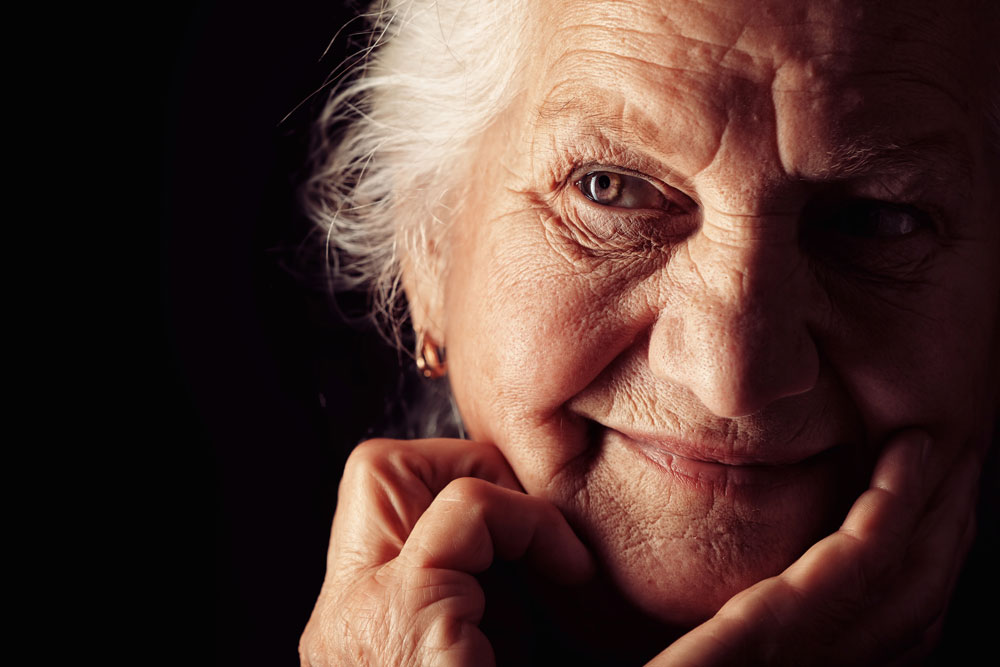 Portrait of a senior woman on black background who is a part of Neurological Rehab program