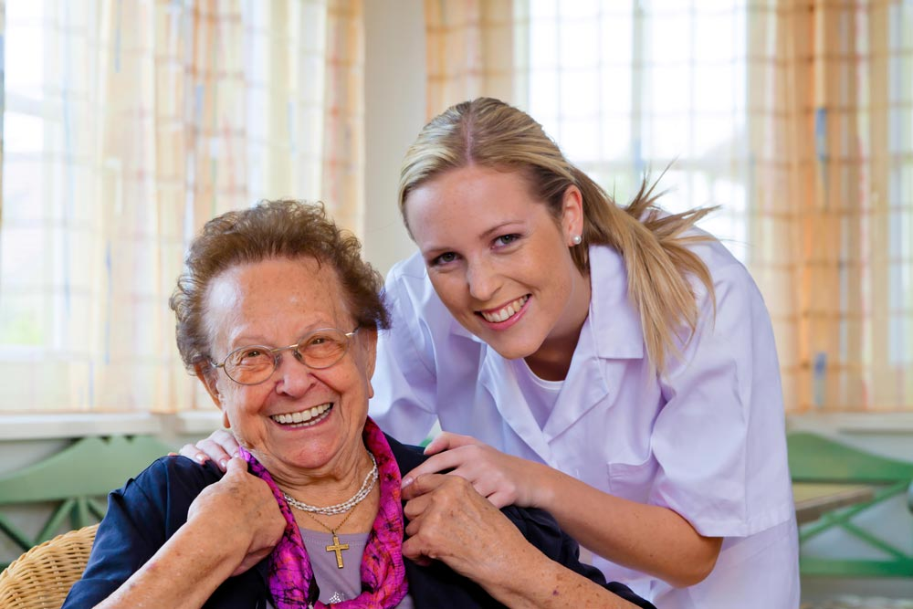 Young female nurse providing leisure activities to an elderly woman
