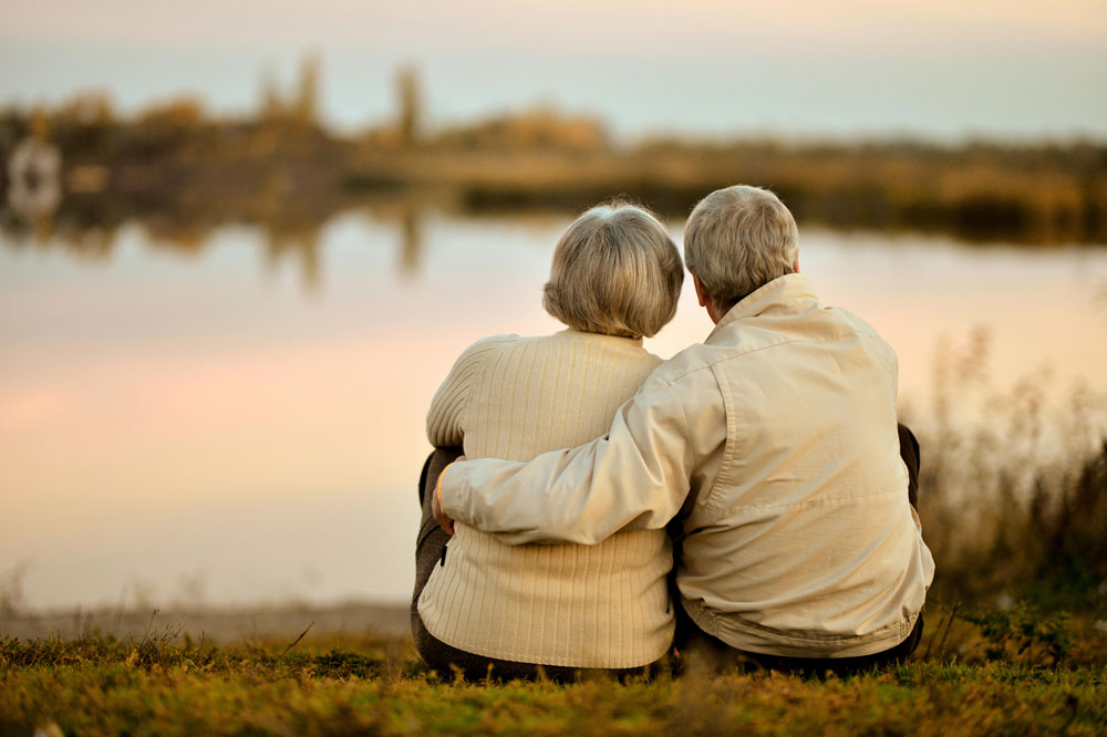 Elderly couple suffering from Parkinson's disease caring for each other and sitting next to a lake